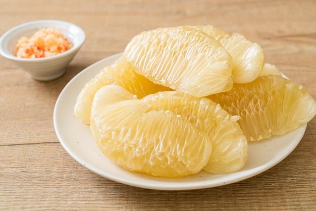 Pomelo fresco descascado, grapefruit ou shaddock em prato branco