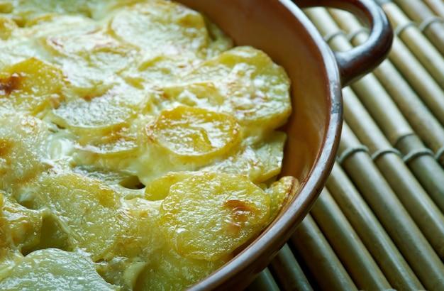 Pommes anna prato francês clássico de batatas fatiadas em camadas cozidas em uma grande quantidade de manteiga derretida.