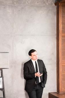 Ponderando o empresário bonito com smartphone a desviar o olhar