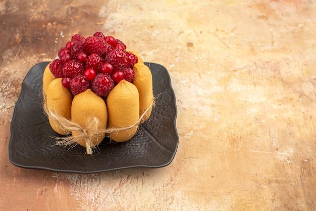 Ponha a mesa para o café e a hora do chá com framboesas em bolos em uma bandeja marrom na mesa de cores diferentes