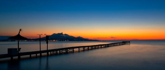 Pontão ao nascer do sol na praia de muro, maiorca, sapin