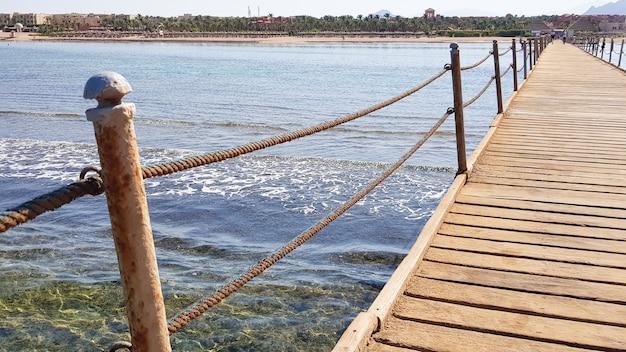 Pontão longo no mar vermelho, no egito. pontão para descida na água. ponte de madeira no território do amway hotel em sharm el sheikh com cercas de metal e uma corda sobre o mar com ondas.