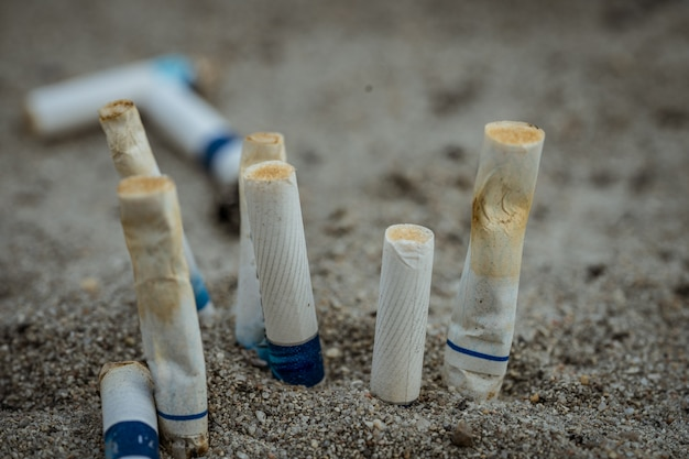 Pontas de cigarro após o uso e, em seguida, à esquerda na areia