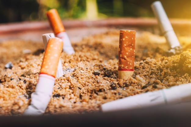 Pontas de cigarro em panelas de areia, conceito não fumar