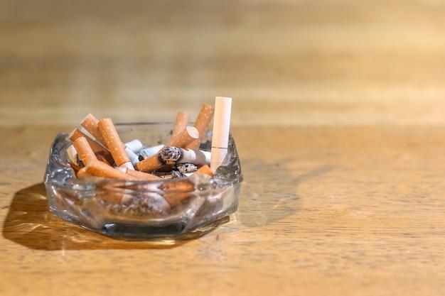 Pontas de cigarro no cinzeiro na mesa de madeira