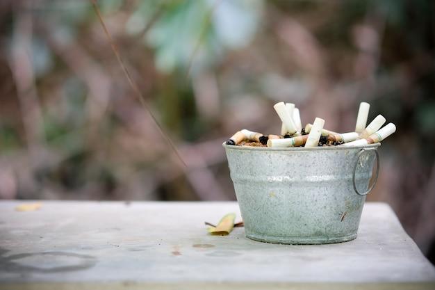 Pontas de cigarro são muitos em pote de zinco cinzeiro