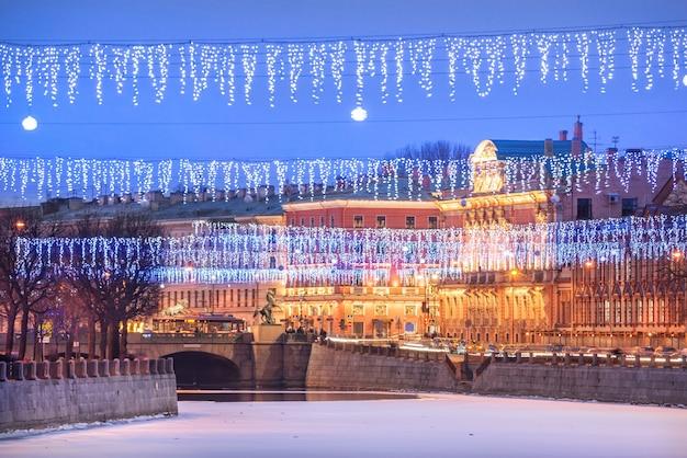 Ponte anichkov sobre o rio fontanka e decorações de ano novo no céu de são petersburgo em uma noite azul de inverno