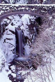 Ponte coberta de neve e margem do rio com cascata no fundo