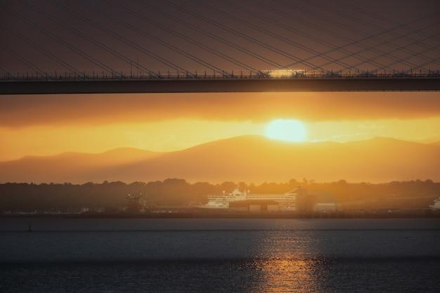 Ponte contra um navio, o sol poente e o mar em frente à estrada, brtidge e queensferry, cruzando a escócia ...