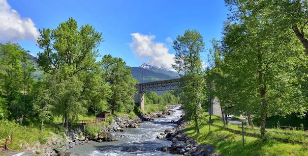 Ponte cruzando as águas correntes de um rio em um vale de tarentaise nos alpes franceses