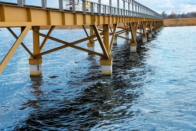 Ponte de aço ao longo da margem do rio, céu azul ao fundo