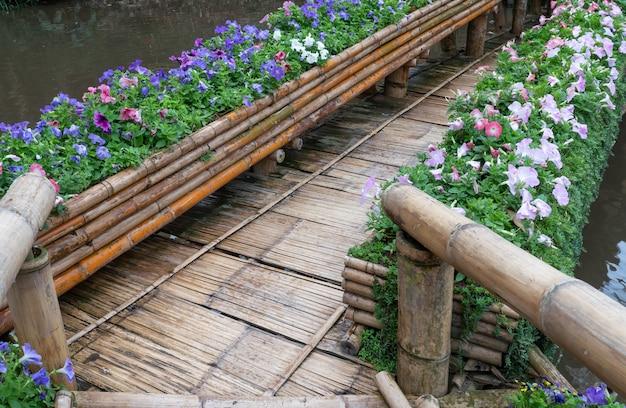 Ponte de bambu velha com a fileira da flor.