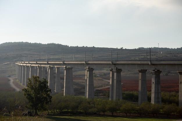 Ponte de concreto em um campo cercado por vegetação com colinas ao fundo
