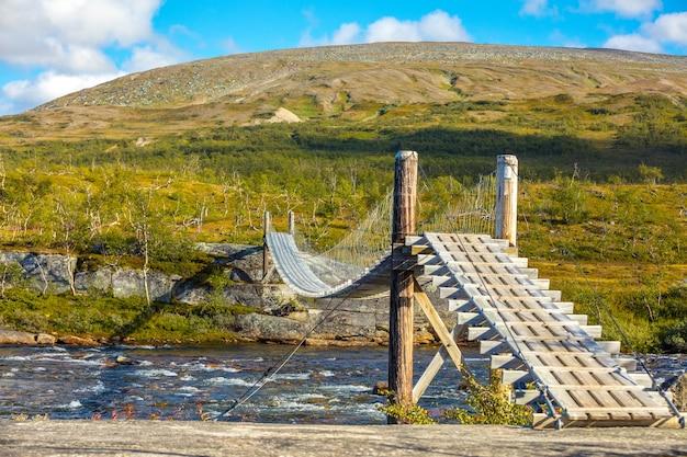 Ponte de madeira com corda suspensa sobre o rio da montanha