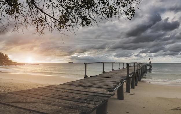 Ponte de madeira do mar e nuvens chuvosas com iluminação do nascer do sol.