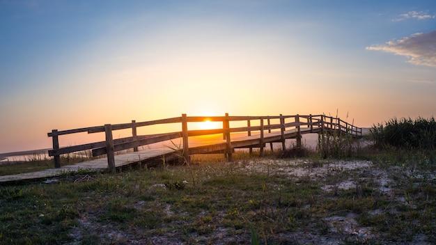 Ponte de madeira em um campo com um lago durante o pôr do sol em portugal