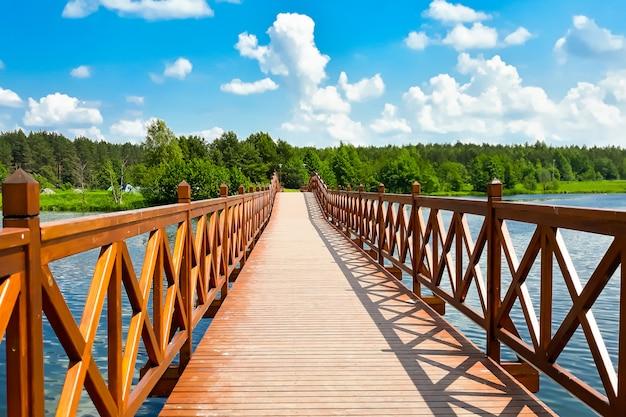 Ponte de madeira em um fundo de céu azul com nuvens