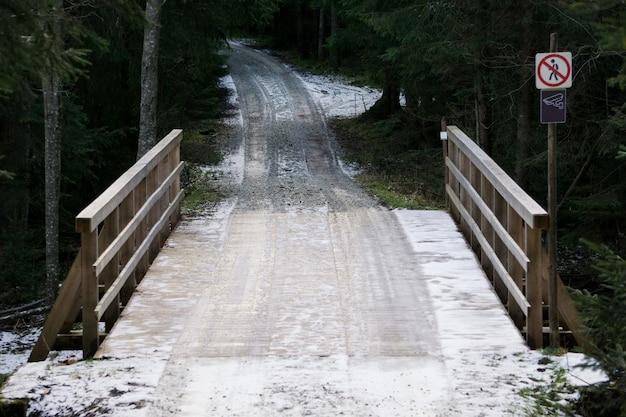 Ponte de madeira na floresta. estrada coberta de neve