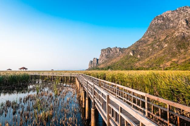 Ponte de madeira no lago e no lanscape da montanha no por do sol no parque nacional de khao sam roi yot, tailândia.