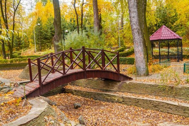 Ponte de madeira no parque outono com gazebo