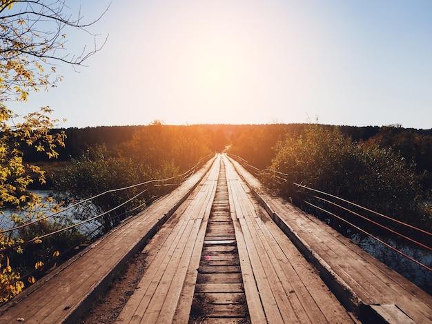 Ponte de madeira para carros e pedestres em clima ensolarado de outono.