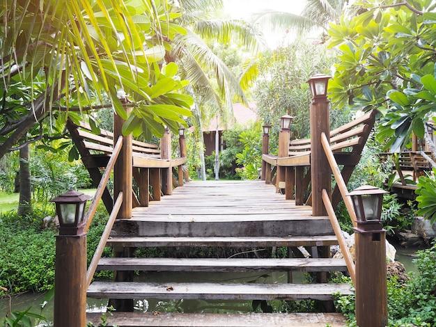 Ponte de madeira que cruza o canal pequeno na decoração verde do jardim.