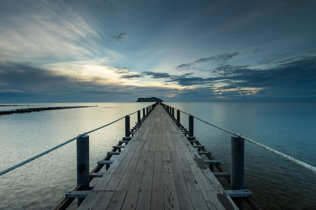Ponte de madeira que se estende até o mar para ser usada para embarcar no barco no píer thung makham noi, chumphon, tailândia