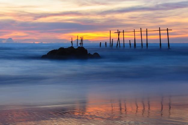 Ponte de madeira quebrada e ondas quebrando no mar durante o pôr do sol, phangnga, tailândia