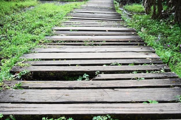 Ponte de madeira quebrada velha e suja no caminho a pé