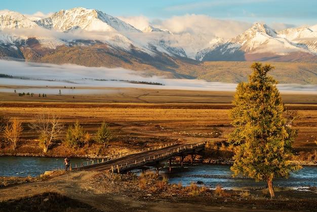 Ponte de madeira sobre o rio chuya na estepe kurai. cume norte de chuysky no horizonte. altai, rússia