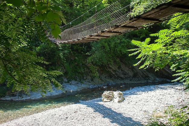 Ponte de madeira suspensa sobre o rio da pequena montanha na floresta