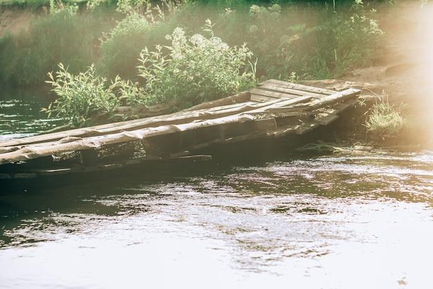 Ponte de madeira torta inclinada sobre um pequeno rio, feita de tábuas velhas