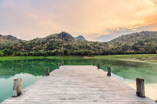 Ponte de madeira vazia ou cais com montanha no lago à noite