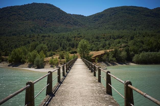 Ponte de pedestres de concreto em uma baía entre colinas verdes