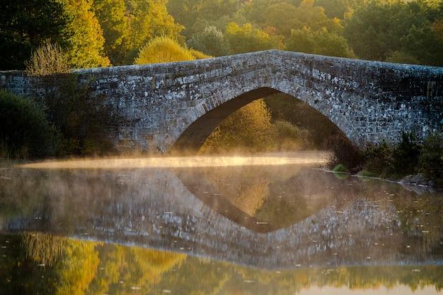 Ponte de pedra romana, com reflexo na água e raios de sol entrando por baixo e com névoa, névoa