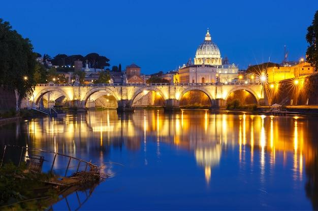 Ponte de santo anjo e a catedral de são pedro com um reflexo de espelho no rio tibre durante a hora azul da manhã em roma, itália.