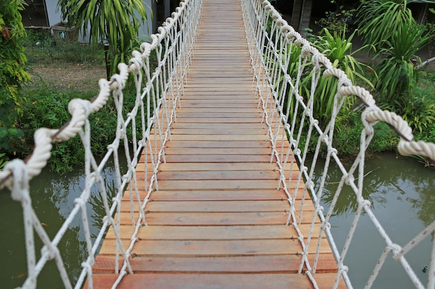 Ponte de suspensão de madeira da corda para o rio do cruzamento da caminhada.