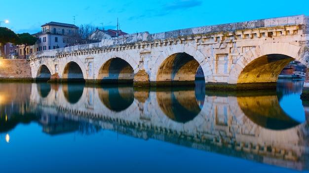 Ponte de tibério em rimini ao entardecer e seu reflexo no espelho de guerra, itália