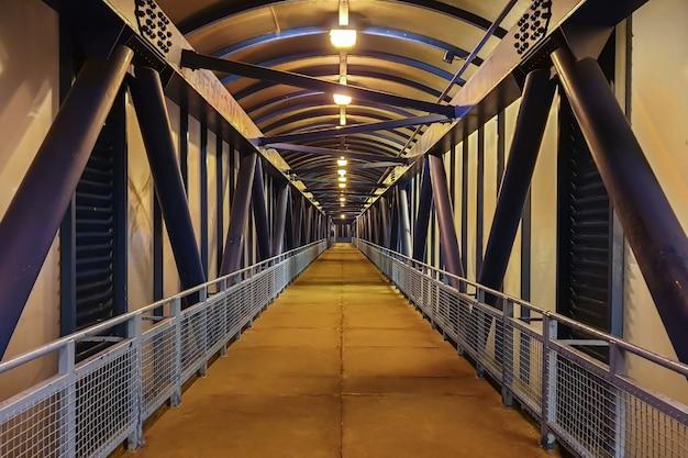 Ponte de vidro pedonal de metal sobre o viaduto. túnel aéreo interno para passagem de pedestres