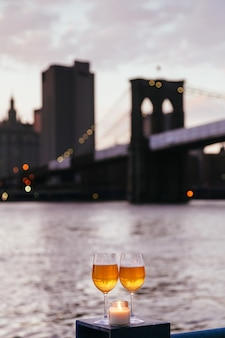 Ponte do brooklyn no crepúsculo das taças de champanhe à vela na cidade de nova york