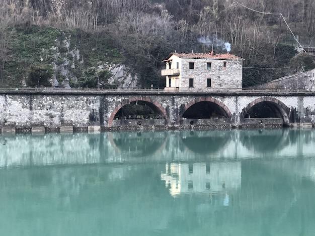Ponte do diabo cercada por colinas cobertas de vegetação e casas refletindo na água na itália