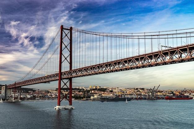Ponte em lisboa durante o pôr do sol, horizonte de portugal e paisagem urbana às margens do rio tejo.