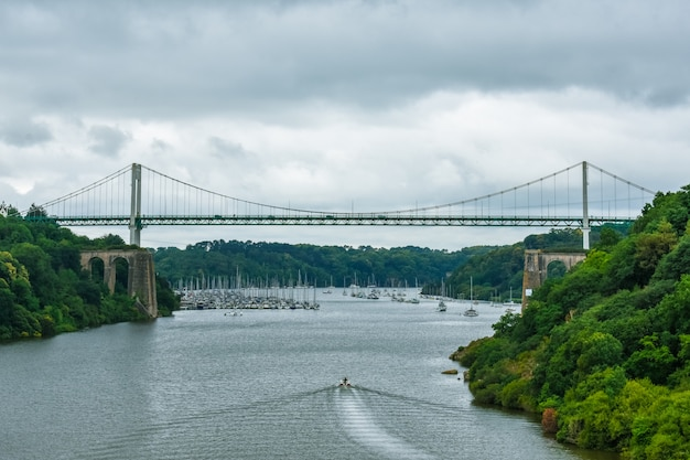 Ponte estaiada em uma floresta natural verde, com um céu nublado dramático. lancha navegando no rio