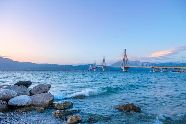 Ponte estaiada grega sobre o golfo de corinto. rion-antirion. céu claro ao anoitecer na costa da montanha