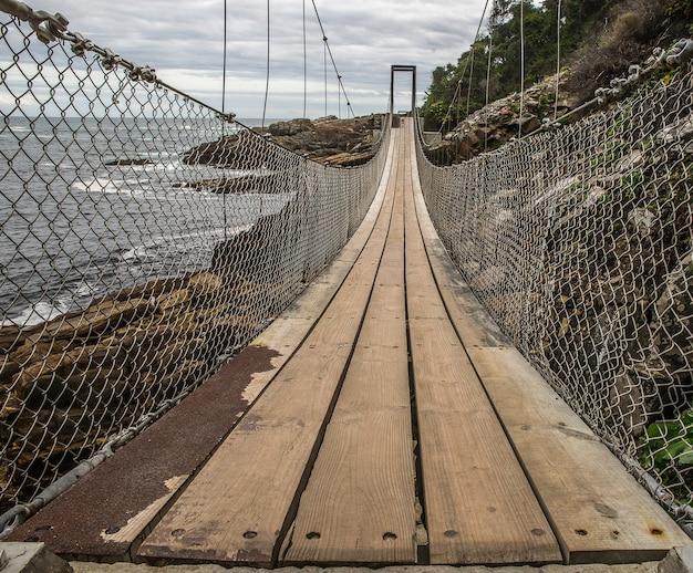 Ponte feita de madeira e metal contornando a montanha ao lado da praia