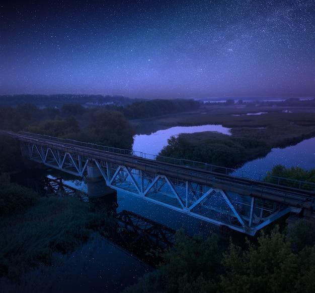 Ponte ferroviária sobre o rio em um fundo de céu estrelado. paisagem linda de verão à noite.