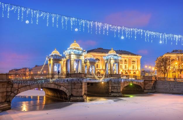 Ponte lomonosov sobre o rio fontanka e decorações de ano novo no céu de são petersburgo