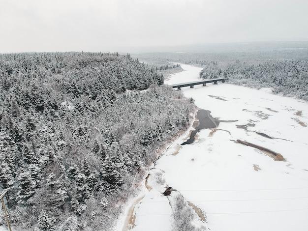 Ponte no rio perto da floresta coberta de neve