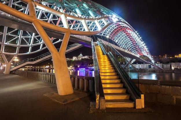 Ponte pedonal da paz sobre o rio mtkvari (kura) em tbilisi à noite