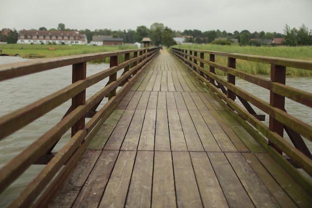 Ponte pedonal de madeira longa com trilhos do outro lado do rio.